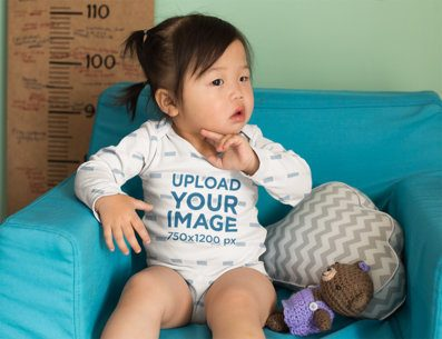 Onesie Mockup of a Baby Girl Sitting on a Couch 25128