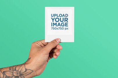 Mockup of a Tattooed Hand Holding a Polaroid 26179