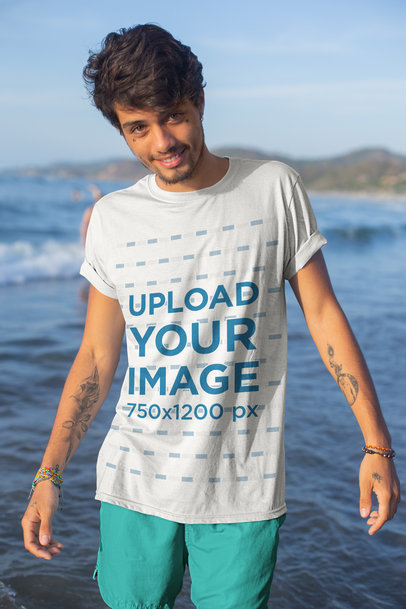 Mockup of a Tattooed Young Man by the Sea Wearing a T-Shirt 26767