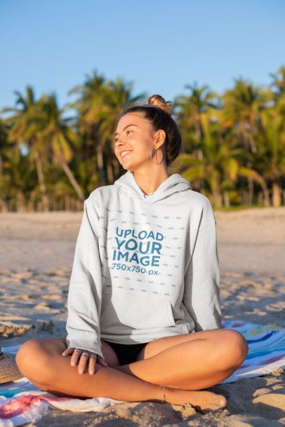 Hoodie Mockup of a Smiling Girl Sitting at the Beach 26805