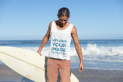 Tank Top Mockup of a Tied-Haired Man Carrying His Surfboard at the Beach 26757