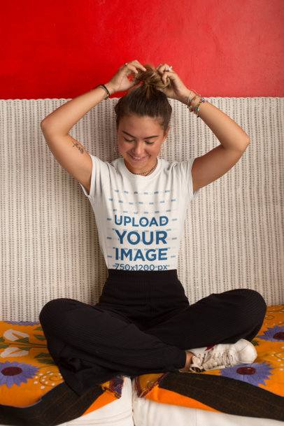 Tee Mockup of a Smiling Woman over a Wicker Couch Fixing Her Hair Bun 26791
