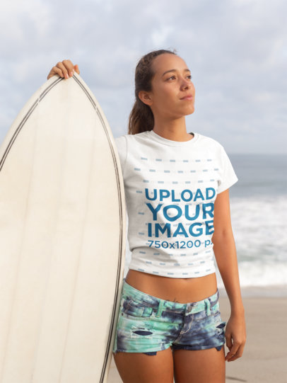 Tee Mockup of a Blonde Woman Standing at the Beach Next to Her Surfboard 26820