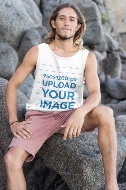 Tank Top Mockup of a Long-Haired Man Sitting over a Breakwater Rock by the Beach 26795