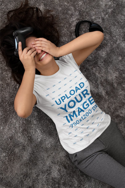 T-Shirt Mockup of a Gamer Woman Lying on a Carpet While Covering Her Face 26998
