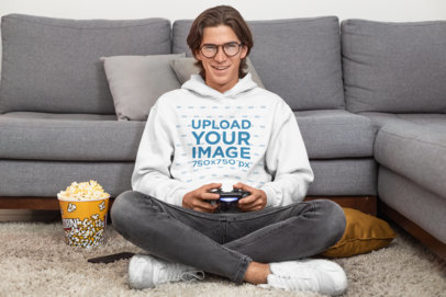 Pullover Hoodie Mockup of a Man Playing Videogames at Home with a Popcorn Bucket 26908