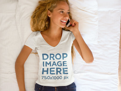 Young Woman Lying in Bed Using an iPhone T-Shirt Mockup a7810