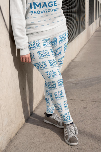 Mockup of a Woman Leaning Against a Concrete Wall Wearing Plus Size Leggings 25004