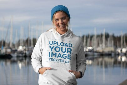 Pullover Hoodie Mockup of a Blonde Woman with a Beanie at the Harbor 25096