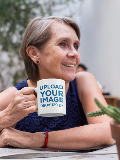 11 Oz Mug Mockup Featuring a Smiling Elderly Woman at a Table 27434