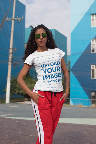 Tee Mockup of a Bold Woman with Sunglasses by Some Apartment Complex 27343
