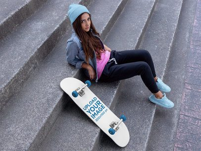 Skateboard Mockup of a Woman with a Beanie Sitting on a Concrete Stairway 27119