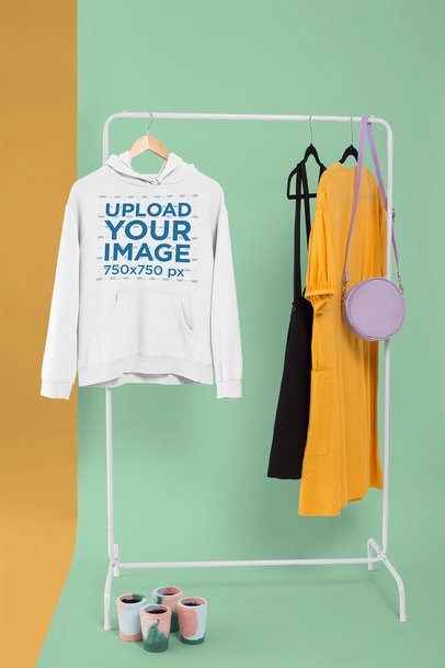 Pullover Hoodie Mockup Hanged from a Rack Along with Casual Dresses 26734
