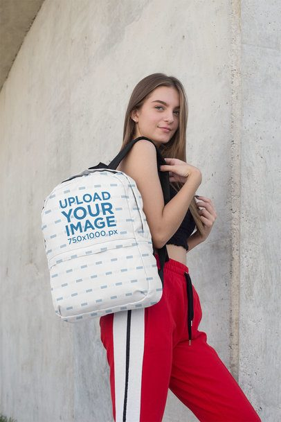 Backpack Mockup Featuring a Teenager Standing Next to a Concrete Wall 27711