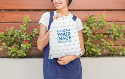 Mockup of a Woman Surrounded by Plants Holding a Drawstring Bag 27587