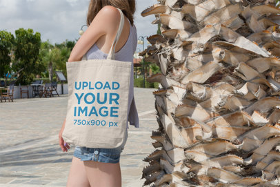 Tote Bag Mockup Featuring a Young Woman Standing Next to a Palm Tree 14-el