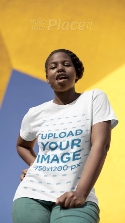 T-Shirt Video Featuring a Joyful Woman Posing in Front of a Yellow Concrete Structure 22999