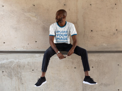 Ringer T-Shirt Mockup Featuring a Cool Young Man Against a Concrete Wall 27897