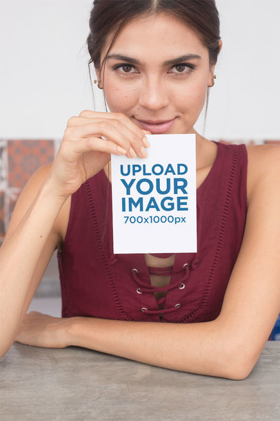 Mockup of a Woman Holding an A6 Flyer While Looking at the Camera 27366