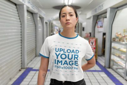Mockup of a Woman Wearing a Ringer T-Shirt in a Market's Hallway 27159
