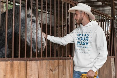 Mockup of a Cowboy Wearing a Pullover Hoodie in a Stable 27960