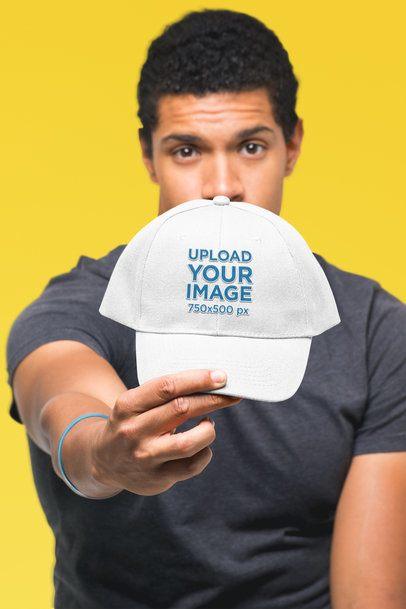 Mockup of a Man Showing off His Dad Hat in a Studio 27046