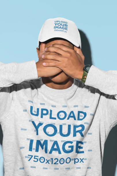 Mockup of a Man Covering His Face Wearing a Dad Hat and a Crewneck Sweatshirt 27058