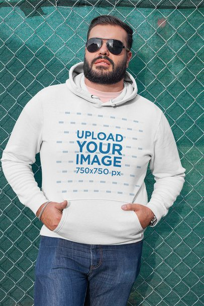 Plus Size Hoodie Mockup of a Man Leaning on a Chain Link Fence 27742