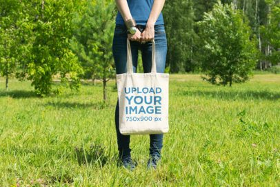 Mockup of a Woman Holding a Tote Bag at an Open Field 24-el