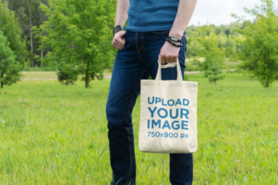 Mockup of a Man Holding a Tote Bag in an Open Field 25-el