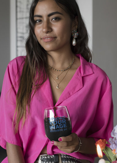 Mockup of a Woman in a Pink Blouse Holding a Stemless Wine Glass 27947