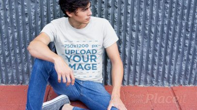 T-Shirt Video Featuring a Young Man Sitting Against a Gray Wall 12136