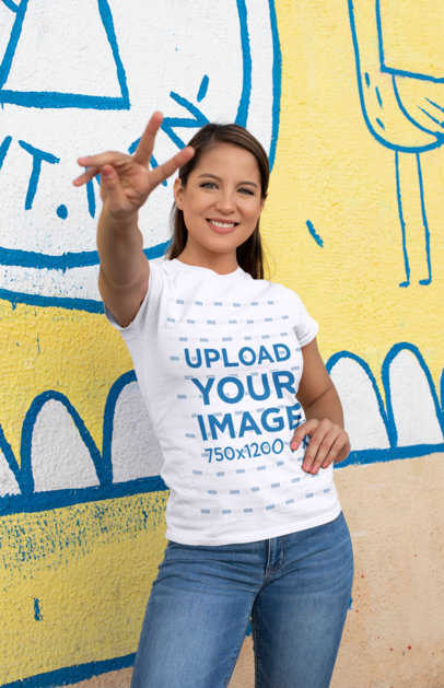 Shirt Mockup of a Woman Doing the Peace Sign Against a Street Art Wall 28203