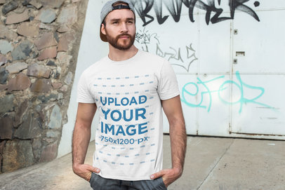 T-Shirt Mockup of a Man Posing in Front of a Graffiti Wall 28200