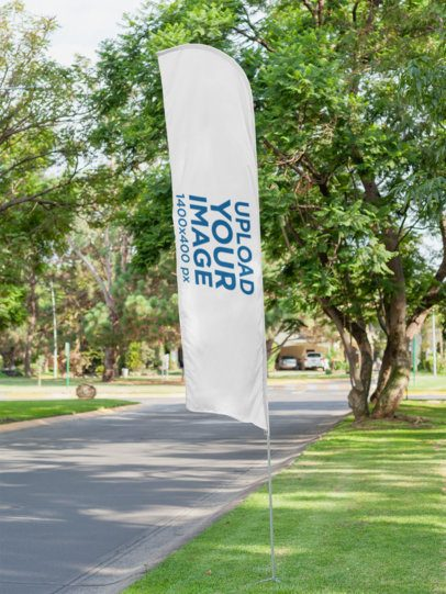 Mockup of a Flag Banner on the Grass Next to a Street 28024