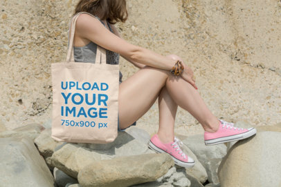 Tote Bag Mockup of a Young Woman Sitting on Rocks in a Sunny Day 108-el