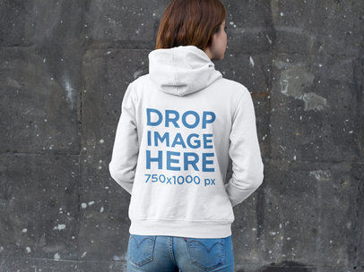 Girl Wearing a Pullover Hoodie Mockup Standing in Front of a Wall a9048b
