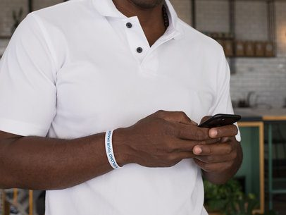 Wristband Mockup of a Man Looking at His Phone 28240