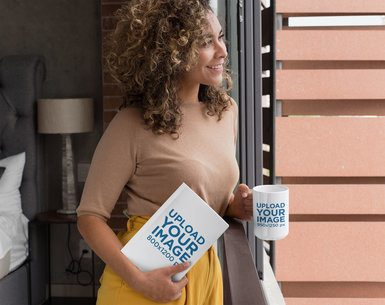 Mockup of a Woman Looking out the Window Holding a 15 oz Mug and a Book 28476