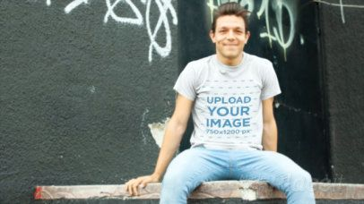 T-Shirt Video of a Man Sitting on a Wooden Platform Against a Graffiti Wall 13031