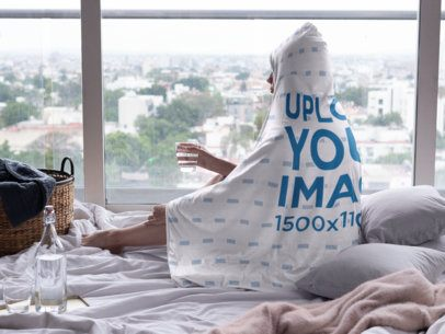 Mockup of a Woman Wearing a Hooded Blanket and Looking out the Window 28146
