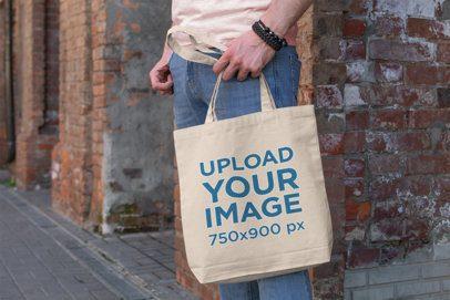 Mockup of a Man Holding a Tote Bag Next to a Brick Wall 192-el