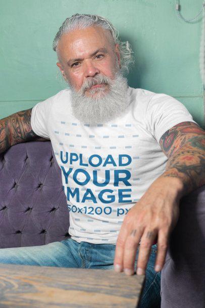 T-Shirt Mockup Featuring a Man Sitting on a Purple Sofa 28417