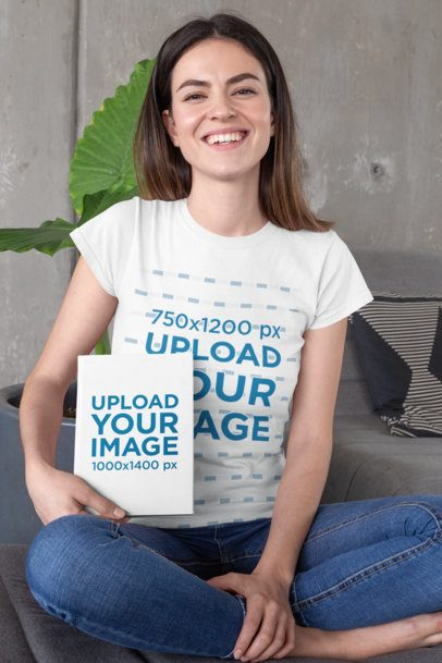 T-Shirt Mockup of a Long-Haired Woman Holding a Book While Sitting on a Couch 28484