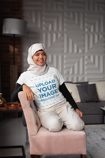 T-Shirt Mockup of a Woman Wearing a Hijab Sitting on a Couch 28399