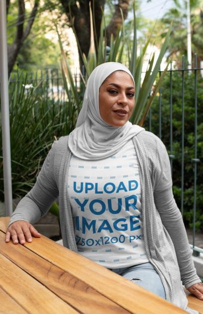 T-Shirt Mockup Featuring a Woman in a Hijab Sitting at a Table 28377