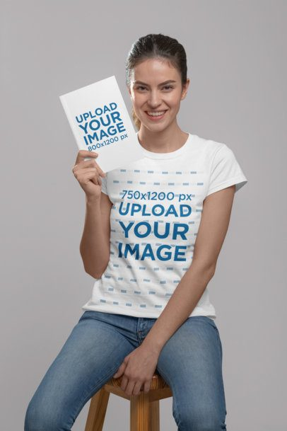 Mockup of a Woman Wearing a T-Shirt and Holding a Book at a Studio 28493