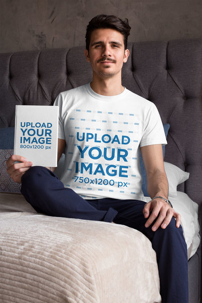 Mockup of a Man Wearing a T-Shirt and Holding a Book in His Bed 28479
