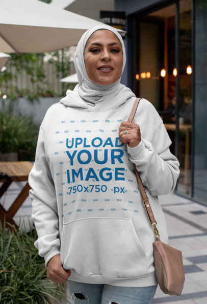 Hoodie Mockup Featuring a Woman with a Hijab Outside a Restaurant 28382