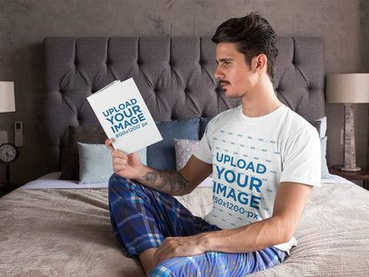 T-Shirt Mockup Featuring a Tattooed Man Reading in His Bedroom 28494